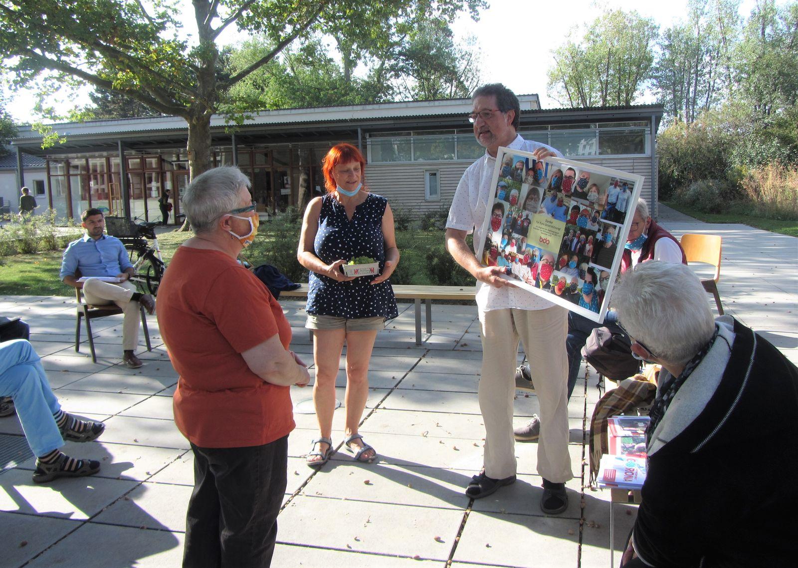 Ulrike Reitz-Nave und Burkhard Tapp überreichen den Bilderrahmen mit Fotos der BDO-Mitglieder und Ihren Familienangehörigen mit Alltagsmasken an Susanne Ruff als Zeichen des Dankes für die Unterstützung der Aktion